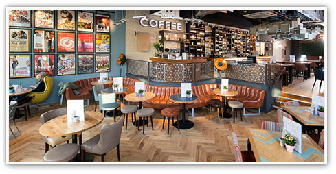 Coffee shop interior with a modern design with eclectic artwork and curved integrated and free-standing tables and seating