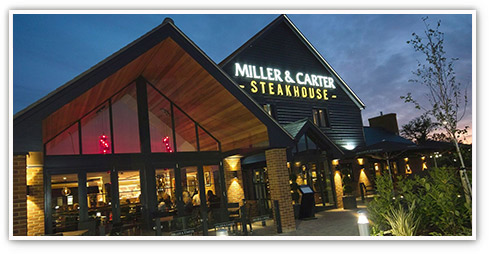 Exterior of a lit up Miller & Carter restaurant at night time