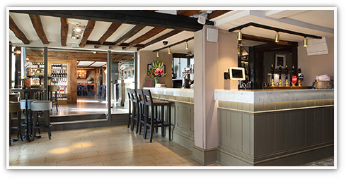Interior of a pub with traditional stone and exposed beams leading to a modern, sleek bar area with bar stools