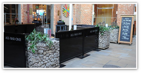 Modern All Bar One exterior with contemporary landscaped features including gabion stone walls adorned with ferns, table height screens and a chalk-board menu