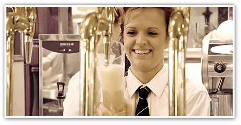 Smiling Browns Bar & Brasserie female team member behind a bar with gleaming beer pumps