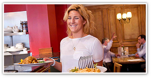 Smiling female team member holding two plates of delicious food ready to serve them in one of Castle's eclectic 'independent' pubs