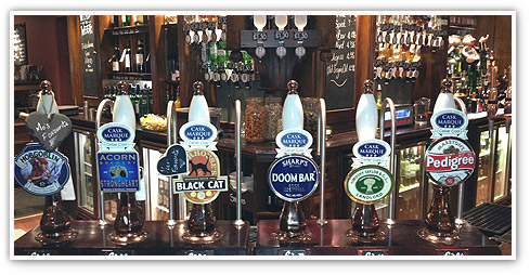 Close up of an Ember Inns bar complete with shining beer pumps showing a variety of real ales and lagers, with a fully stocked bar in the background