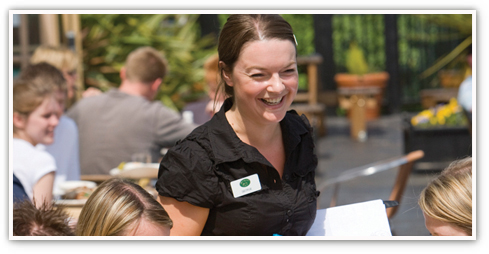 Smiling Harvester female team member serving a group of people at an outside table in the summer
