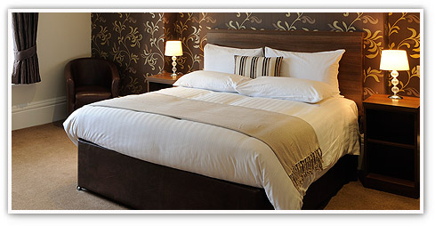 Close up of Innkeeper's Lodge double bed with sumptuous linens and stylish d�cor