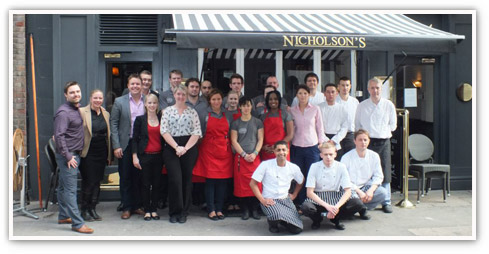 Smiling group of team members, kitchen staff and managers outside a Nicholson's pub