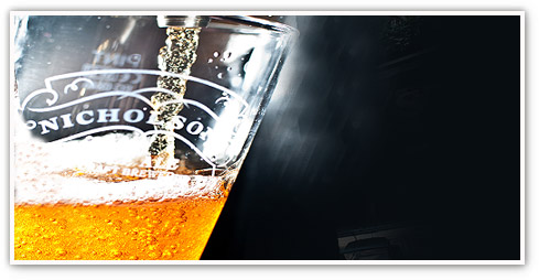 Close up shot of a crisp, cold pint of beer being poured into a Nicholson's pint glass