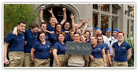 Smiling group of team members, kitchen staff and managers outside an O'Neill's pub holding a chalk sign with 'Céad míle fíilte' written on it, which translates to 'A hundred thousand welcomes'