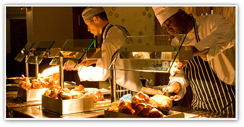 Two male chefs behind the carvery deck slicing freshly prepared roasts in an Orchid Pub