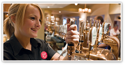 Smiling female team member pulling a pint from a pump at the bar