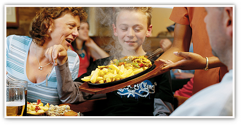 Team member serving a sizzling skillet to a happy young lad with his smiling mum looking on
