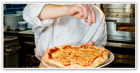 Chef putting the finishing touches to a Stonehouse pizza just before serving