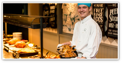 Smiling male chef proudly standing by his Stonehouse carvery deck ready to serve guests