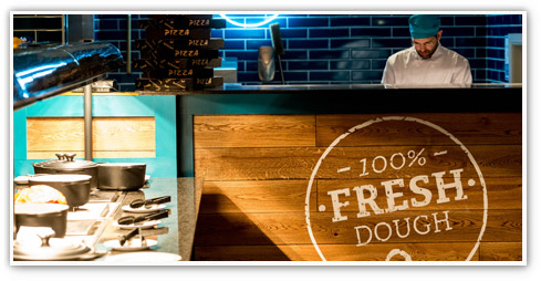 Shot of male chef getting preparing food behind a Stonehouse '100% fresh dough' sign