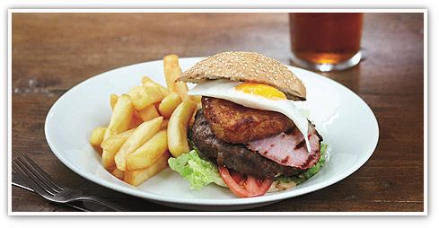 Close up of a burger with extra free-range egg and bacon, with chips available at an Oak Tree pub