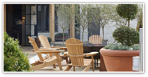 Exterior shot in the garden of a Premium Country Pub with relaxing summer chairs set in a well-kept courtyard garden